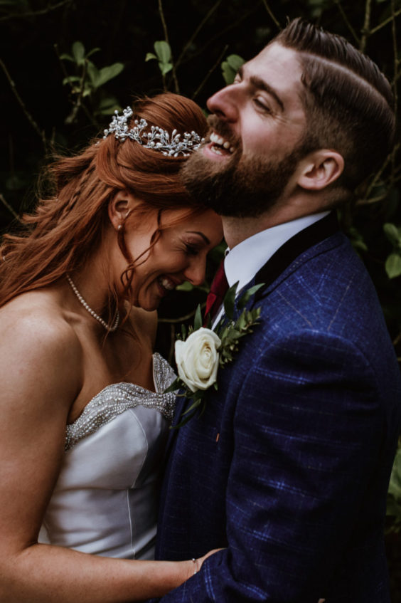 Bride and groom smiling and hugging on wedding day