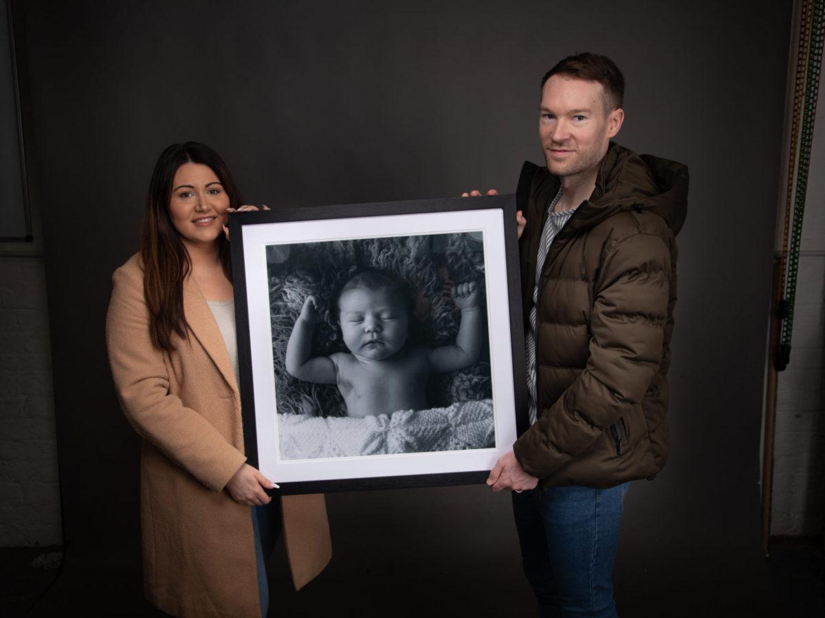 Couple holding newborn portrait at chocolate chip studio